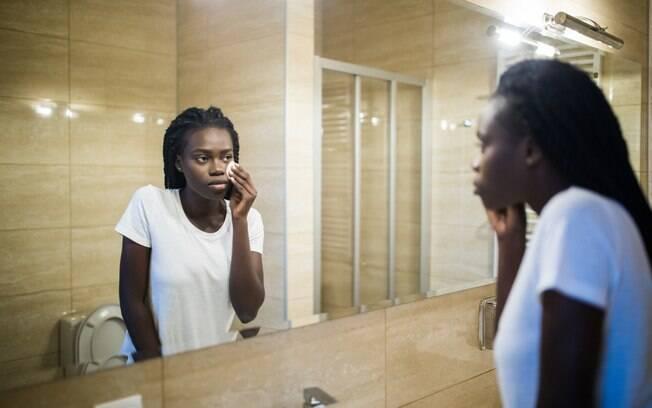 mulher limpando a pele diante do espelho