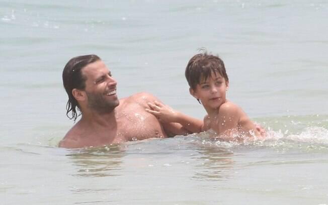 Henri Castelli brinca com Lucas no mar carioca