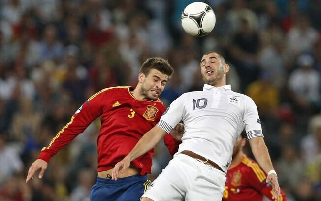 O zagueiro espanhol Piqué, do Barcelona,  disputa a bola pelo alto com o atacante francês  Benzema, do Real Madrid