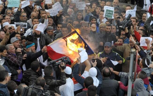 Ativistas queimam uma representação de bandeira francesa durante protesto contra charges publicadas pelo Charlie Hebdo em Argel, Argélia