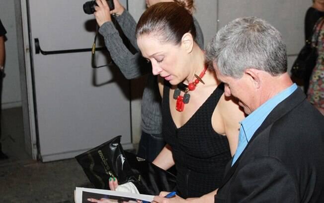 Claudia Raia autografa fotos suas para um fã, na noite de sábado (31)