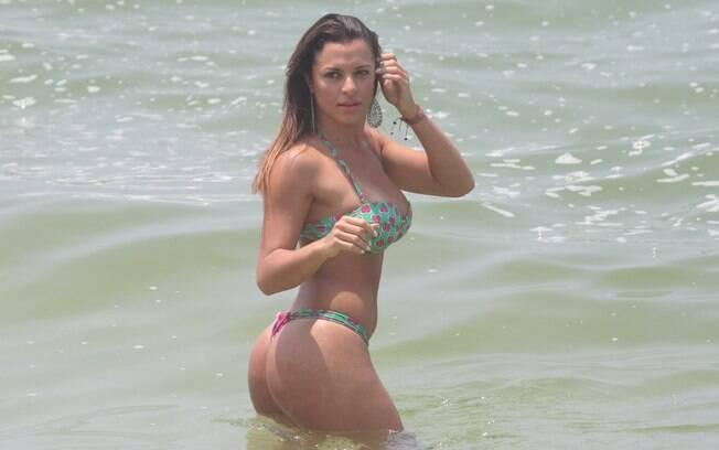 Carol Abranches percebe a presença de paparazzo na praia e faz pose