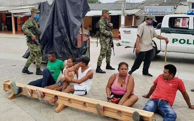 Pessoas que desrespeitaram as normas de isolamento social foram detidas pela polícia local e presas pelos pés