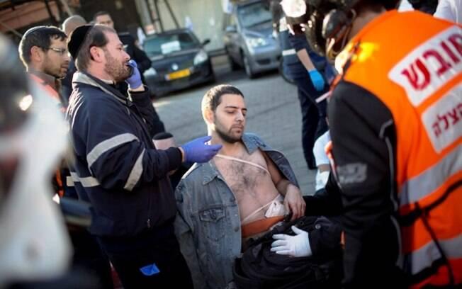Ferido é tratado por paramédicos após ter sido esfaqueado em Tel Aviv, Israel