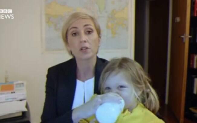 Na paródia, a mãe dá atenção aos filhos, cozinha, limpa e até desativa uma bomba enquanto concede a  entrevista