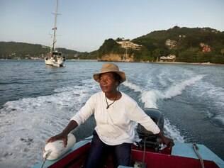 Motorista de barco-táxi maneja a embarcação até a praia Princess Margareth