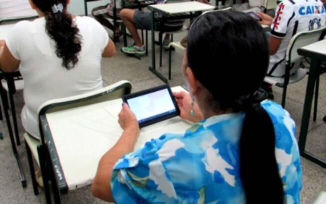 Jovens e adultos usam celular em sala de aula