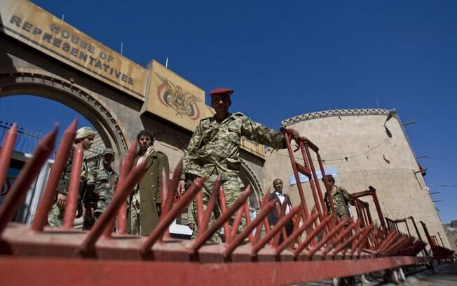 Xiitas iemenitas vestindo uniformes do Exército montam guarda em frente ao Parlamento durante reunião em Sanaa, Iêmen (9/02)