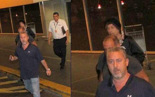 Bob Dylan (de gorro preto) desembarca no aeroporto Galeão, no Rio, na madrugada deste sábado (14)