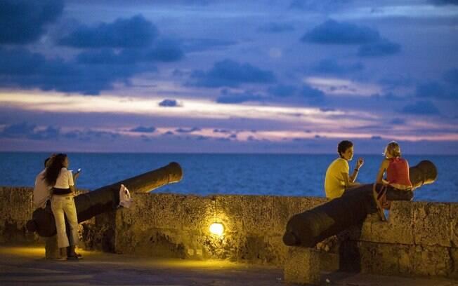 Turistas assistem ao pôr-do-sol da muralha que cerca o centro histórico de Cartagena
