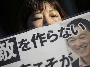Uma mulher segura um cartaz com a foto de Kenji Goto com a frase