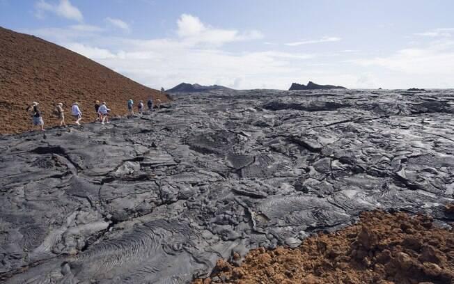 Turistas caminham por chão de lava da Isla Santiago