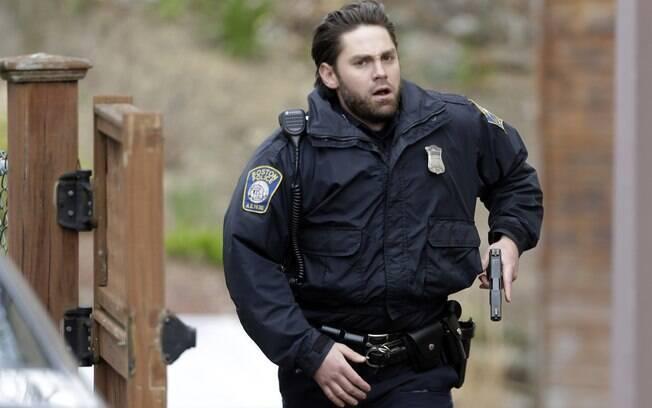 Policial corre com a arma na mão em busca de suspeito em Watertown