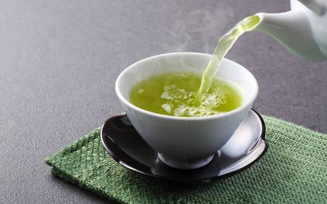 chá verde sendo despejado por um bule em uma caneca