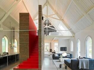 """A escada fica em uma estrutura moderna, revestida com o piso reciclado da igreja, e """"separa"""" a cozinha da sala de estar"""