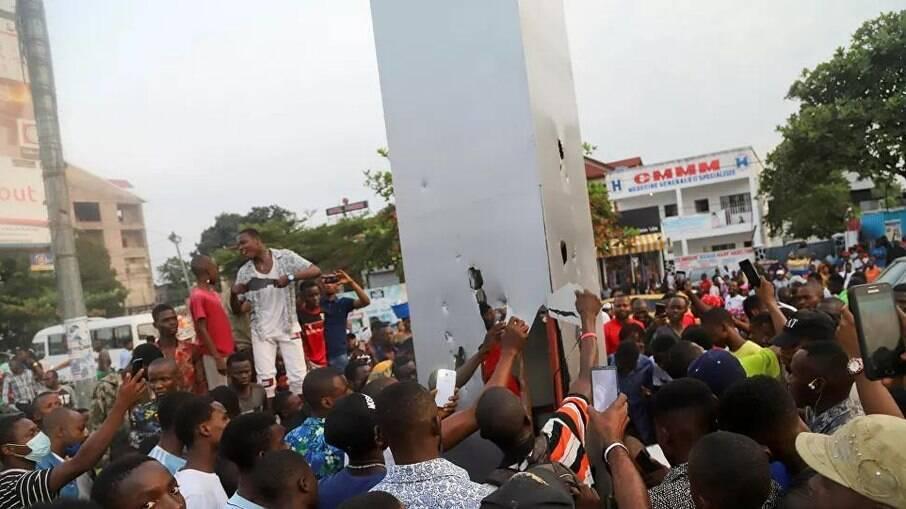 População reagindo a monólito encontrando em capital do Congo, na África