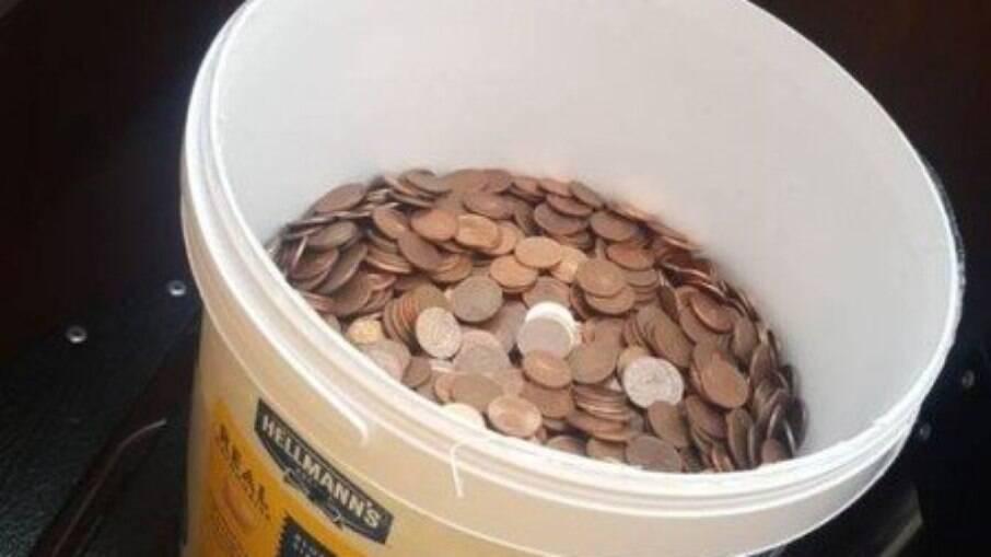 Pagamento em moedas dentro de balde de maionese
