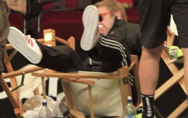 Elton John cai da cadeira em torneio de tênis