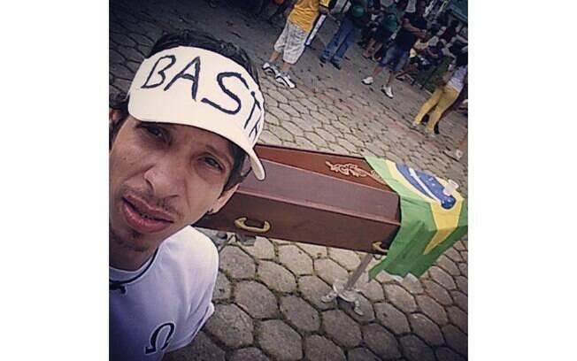 Caixão com bandeira do Brasil é levado por manifestante, durante protesto na Praça da Bíblia, em Goiânia