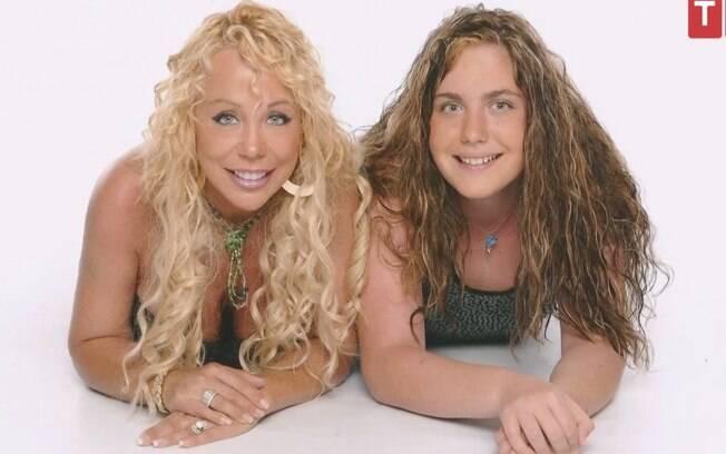 Mary, a mãe, de cabelos loiros e pele bronzeada ao lado de sua filha, Brittani, de cabelos castanhos e pele branca.