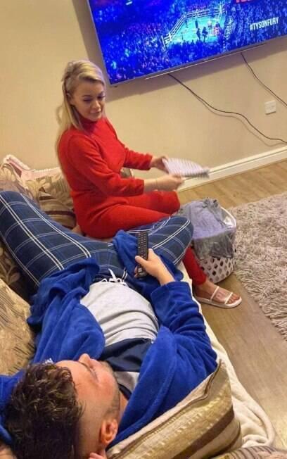 homem deitado no sofá assistindo televisão; mulher olha séria