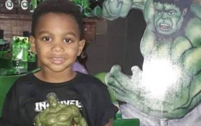 menino de camisa preta sorrindo e segurando um boneco verde
