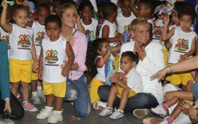 Shakira e Xuxa vistam crianças em creche da Cidade de Deus
