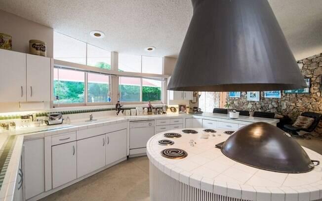 A cozinha possui uma ilha central arredondada para combinar com o formato dos cômodos da casa