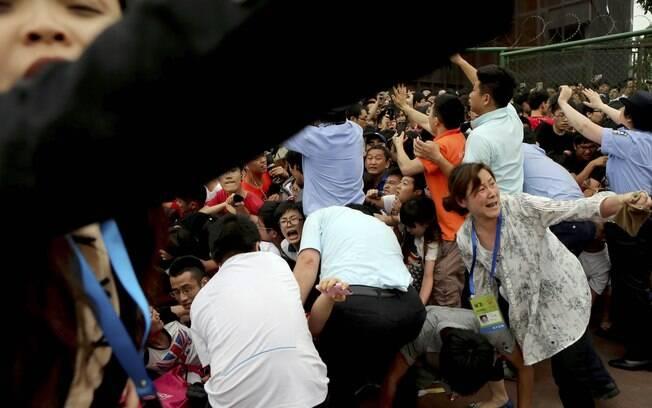 Multidão tentou invadir local quando portão  foi aberto para passagem do carro de Beckham.  Chineses passaram por cima dos policias