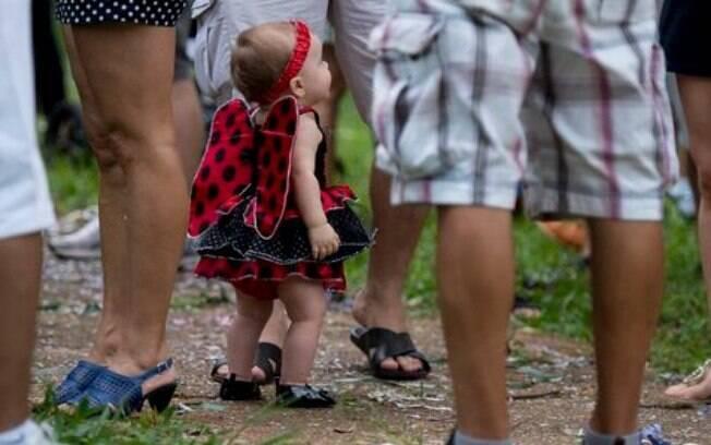 Menina entre adultos que levaram filhos, sobrinhos e netos para pular carnaval em praça no DF