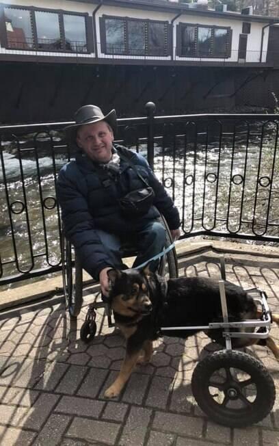 Homem e cão, ambos de cadeira de rodas, posam juntos para foto