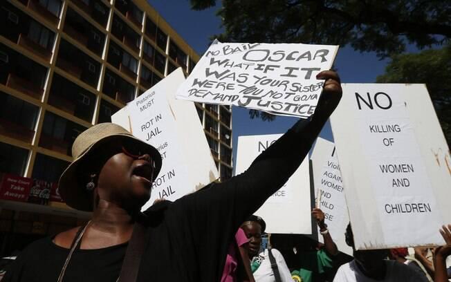 Do lado de fora, pessoas protestam contra  Oscar Pistorius, que teria atirado e matado a  namorada em casa