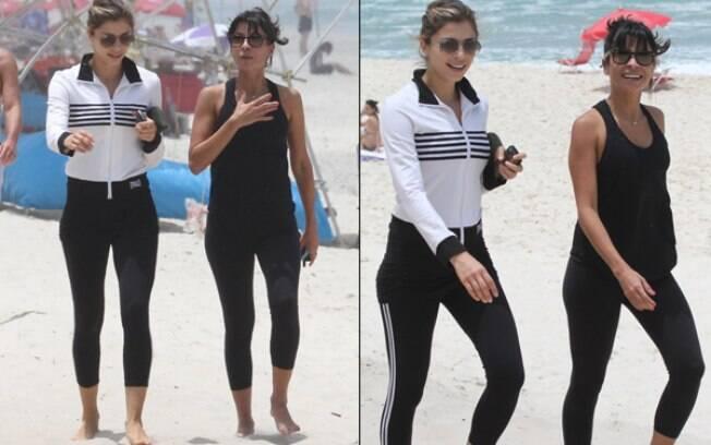 Grazi Massafera e Ana Lima caminham na praia