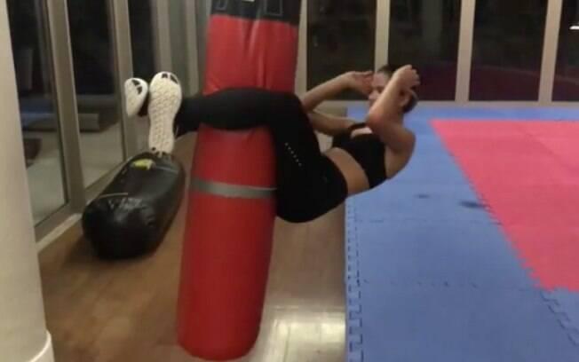 Em um de seus treinos com o personal Chico Salgado, Bruna Marquezine faz um abdominal usando um saco de boxe como apoio para pernas
