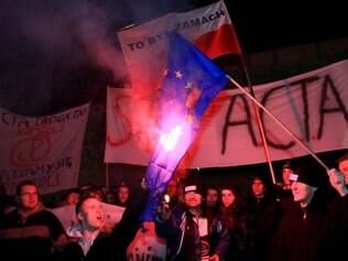 Manifestantes queimam bandeira da União Europeia em protesto contra o ACTA