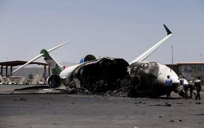 Funcionários de Felix Airways, companhia aérea doméstica, inspecionam avião destruído por ataques aéreos liderados pela Arábia Saudita no aeroporto internacional de Sanaa