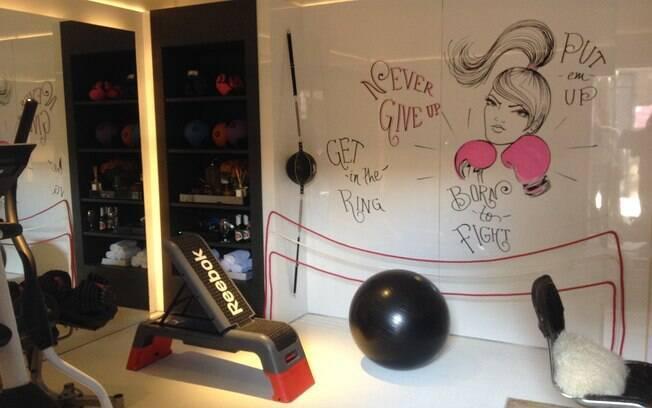 Integrados, o living e a sala de ginástica ganharam tons femininos, como vermelho e rosa. O sofá vintage arremata a composição