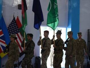 NATO-led International Security Assistance Force (ISAF) soldiers carry flags during a ceremony marking the end of ISAF's combat mission in Afghanistan at ISAF headquarters in Kabul on December 28, 2014. NATO formally ended its war in Afghanistan on December 28, holding a low-key ceremony in Kabul after 13 years of conflict that have left the country in the grip of worsening insurgent violence.The event was arranged in secret due to the threat of Taliban strikes in the Afghan capital, which has been hit by repeated suicide bombings and gun attacks over recent years.
