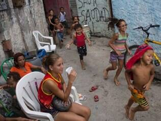 Young residents play in an alley after a police operation at Nova Holanda, part of the Mare slum complex in Rio de Janeiro, Brazil, Sunday, March 30, 2014. The Mare complex of slums, home to about 130,000 people and located near the international airport, is the latest area targeted for the government's