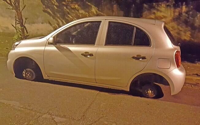 Nissan March 1.0  sem as rodas do lado esquerdo, alvo de furto de rodas. A avaliação do carro teve que ser interrompida
