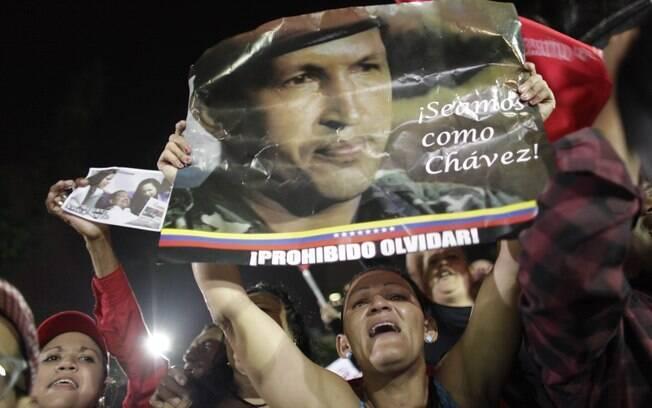 Partidários de Hugo Chávez seguram cartaz em que se leem 'Sejamos como Chávez' e 'Proibido esquecer' durante homenagem a líder venezuelano, morto nesta terça, em Caracas (05/03)