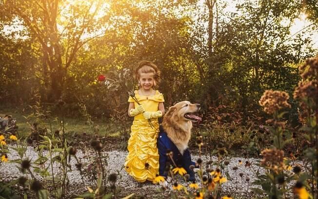 Menina fantasiada de bela ao lado de cachorro fantasiado de fera