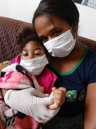 Mulher sentada no sofá com sua filha no colo, ambas usando máscara de proteção