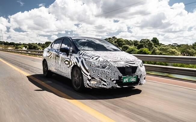 Novo Nissan Versa chegará ao Brasil em novembro e tem a primeira imagem rodando em testes, ainda camuflado, antes da estreia