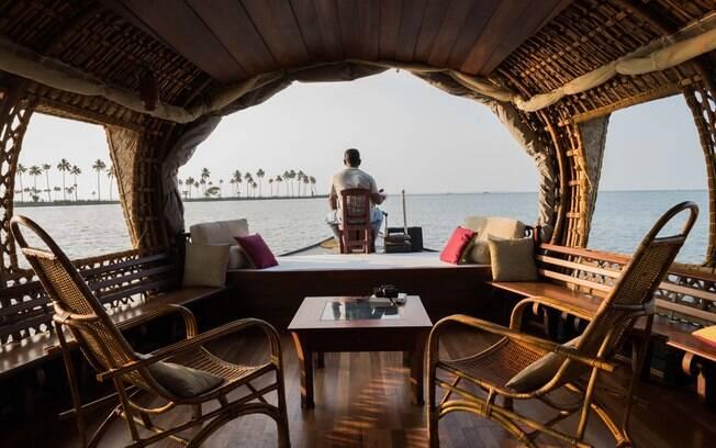 Homem sentado em na proa de um dos barcos da Xandari Riverscapes