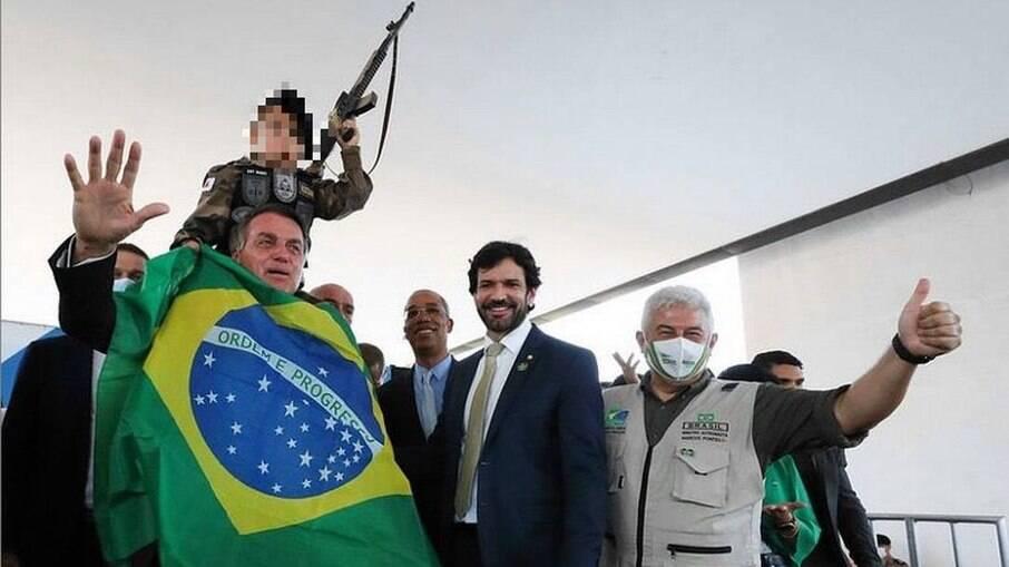 Jair Bolsonaro carrega uma criança com réplica de arma