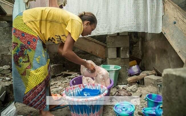 Mãe dá banho em seu filho albino na Tanzânia. Número de pessoas com essa característica é alto no país (2013). Foto: Tanzania Albinism Society