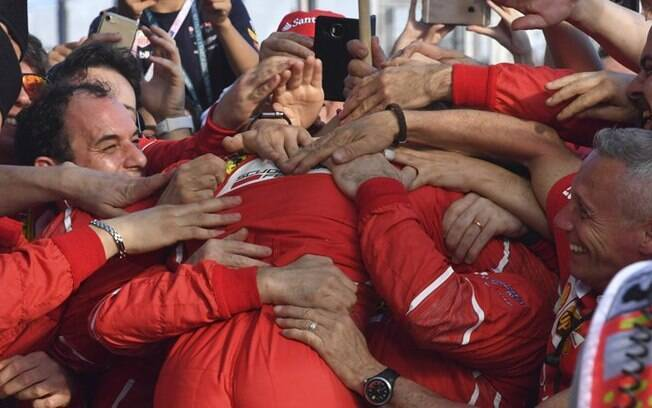 Vettel é abraçado pelos companheiros da Ferrari após a vitória