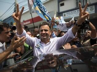 Aecio Neves, presidential candidate of the Brazilian Social Democracy Party, PSDB, flashes a victory sign as he campaigns at the