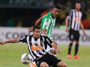 Alexander Mejia, of Colombia's Atletico Nacional, back, challenges Leandro Donizete, of Brazil's Atletico Mineiro, during a Copa Libertadores soccer match in Medellin, Colombia, Wednesday, April 23, 2014. (AP Photo/Ricardo Mazalan)